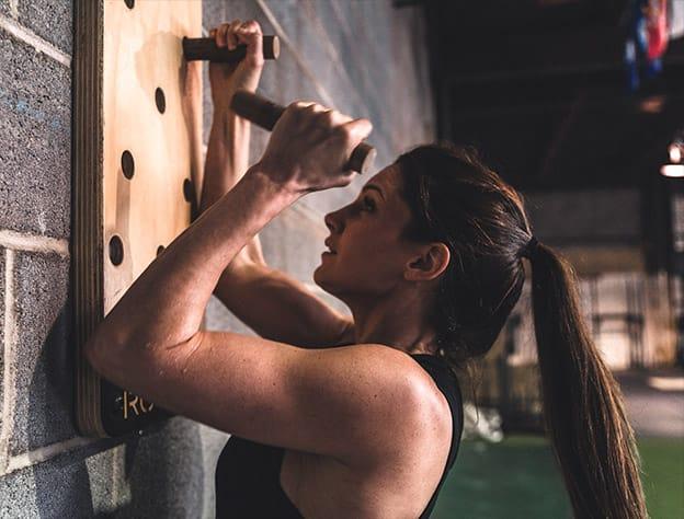 Female athelete climbing wall