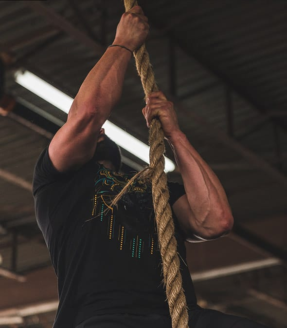 Athlete climbing rope